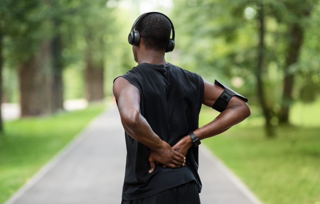 Back view of black man in sportswear standing in park and touching injured back