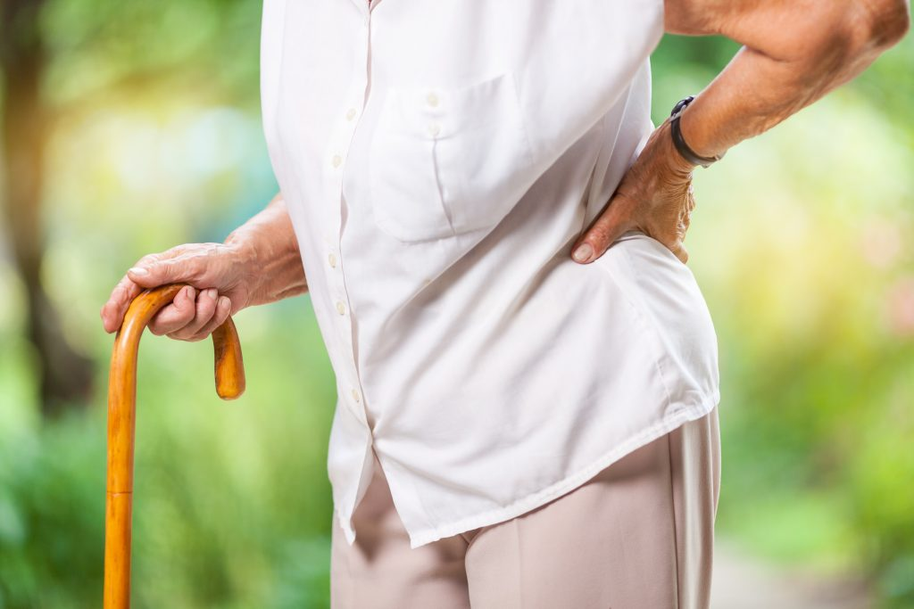 Elderly woman outdoors with lower back pain