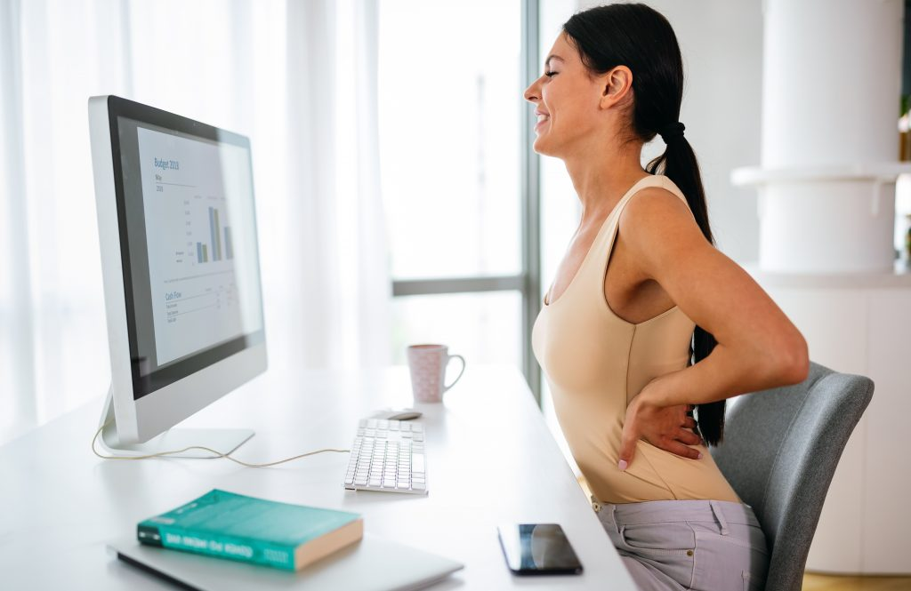 Overworked tired woman with back pain in office with bad posture